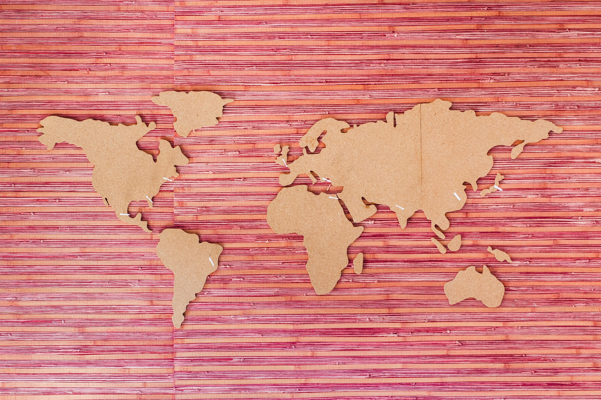 Cut out map of the world on top of a wooden backing