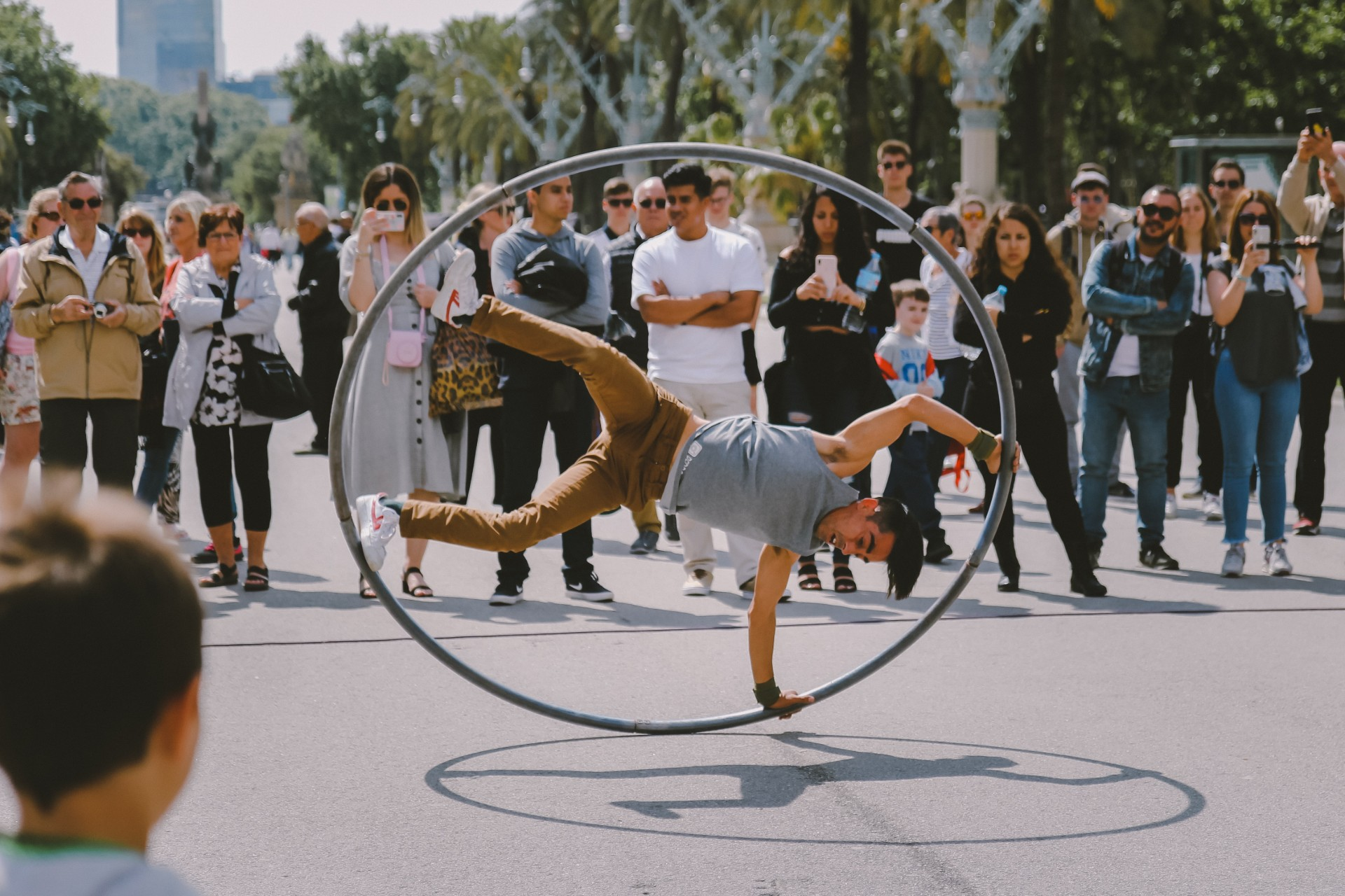 Street preformer in a hoop is watched by crowd