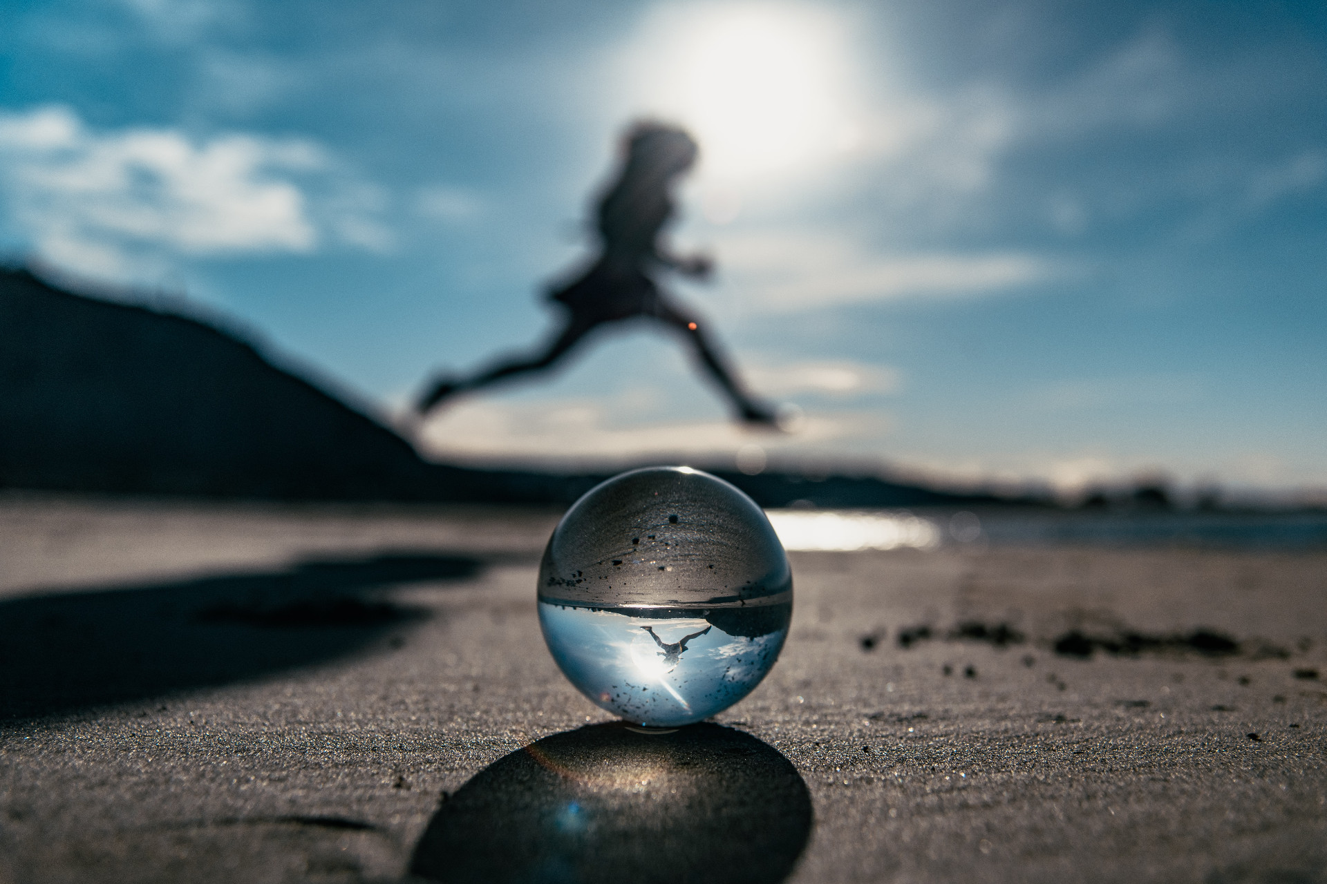 Shadow of a person jumping over a crystal ball