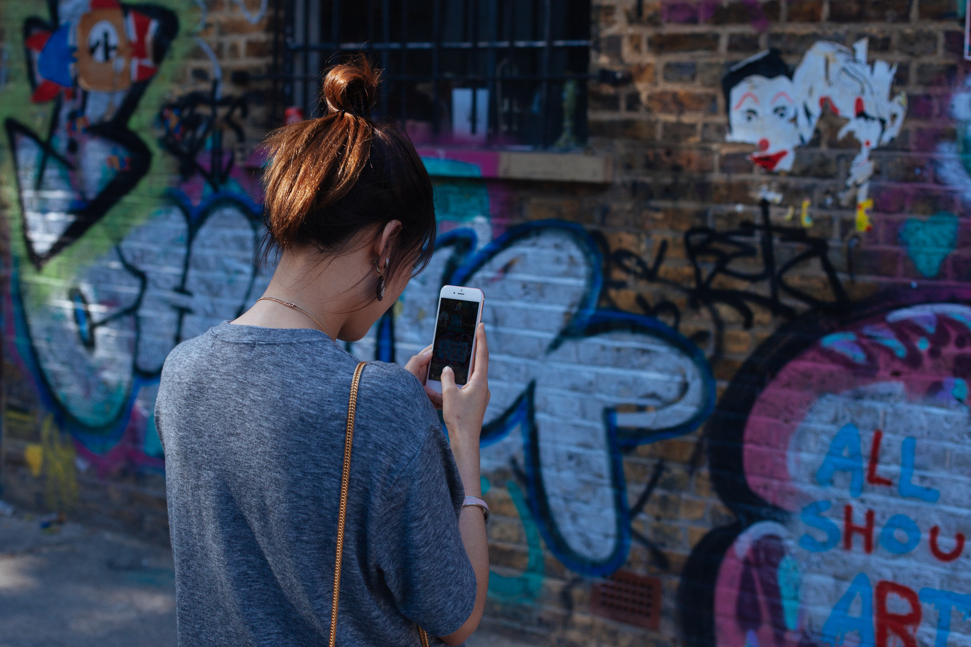 A girl taking a photo of a mural with graffiti
