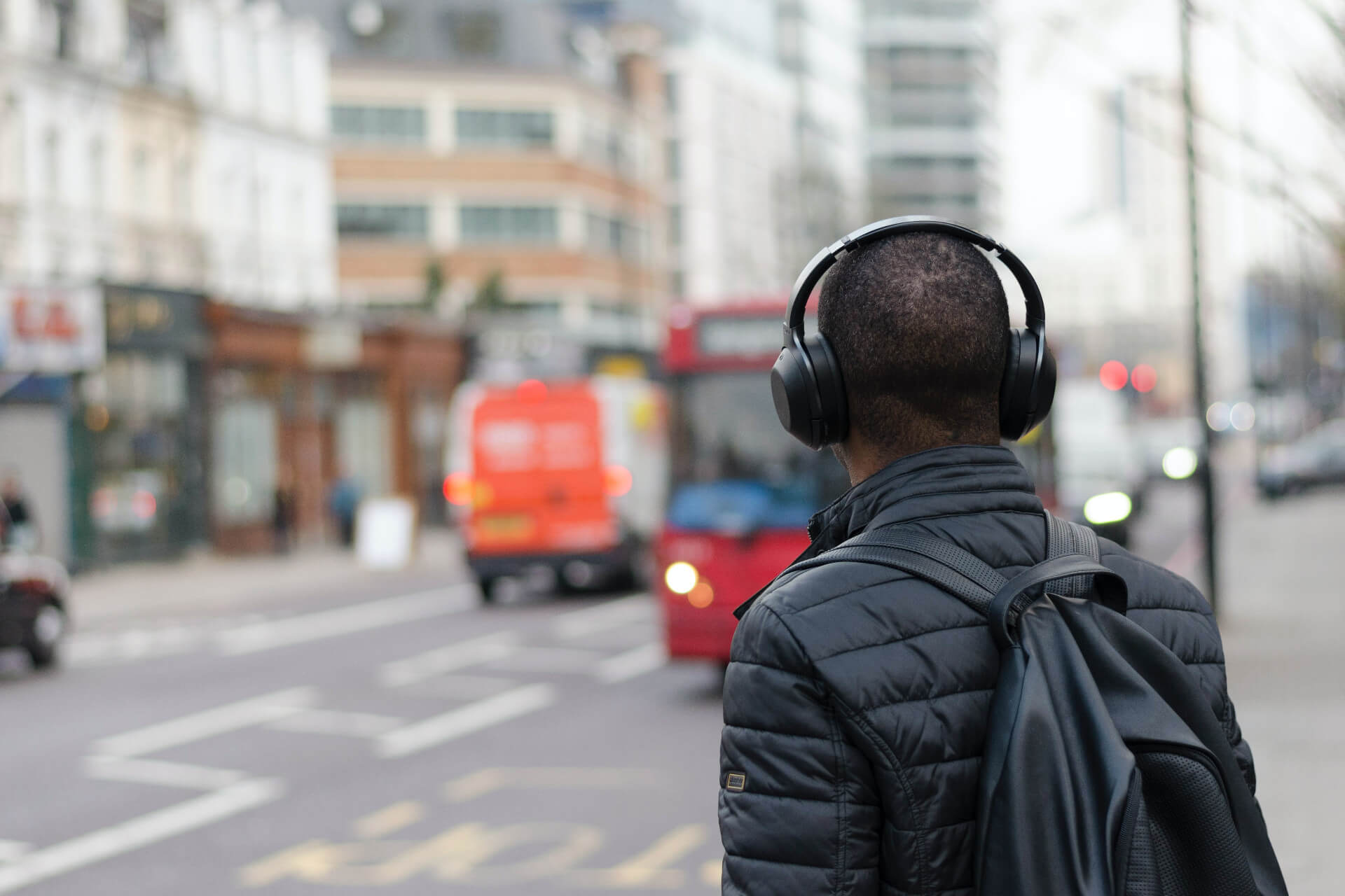 A man walking down a street weating headphones