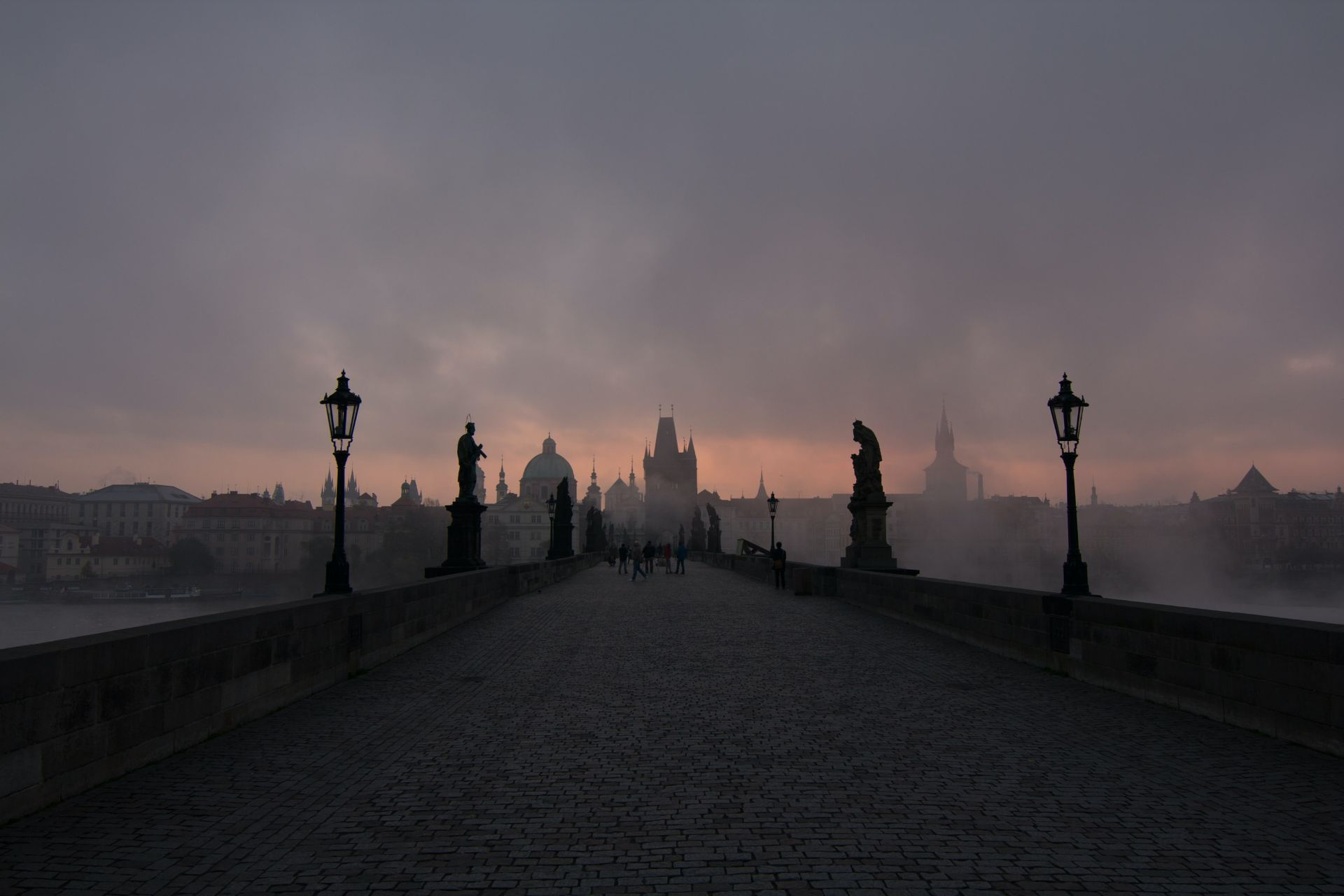 The pink sun rising over Charles Bridge in Prague