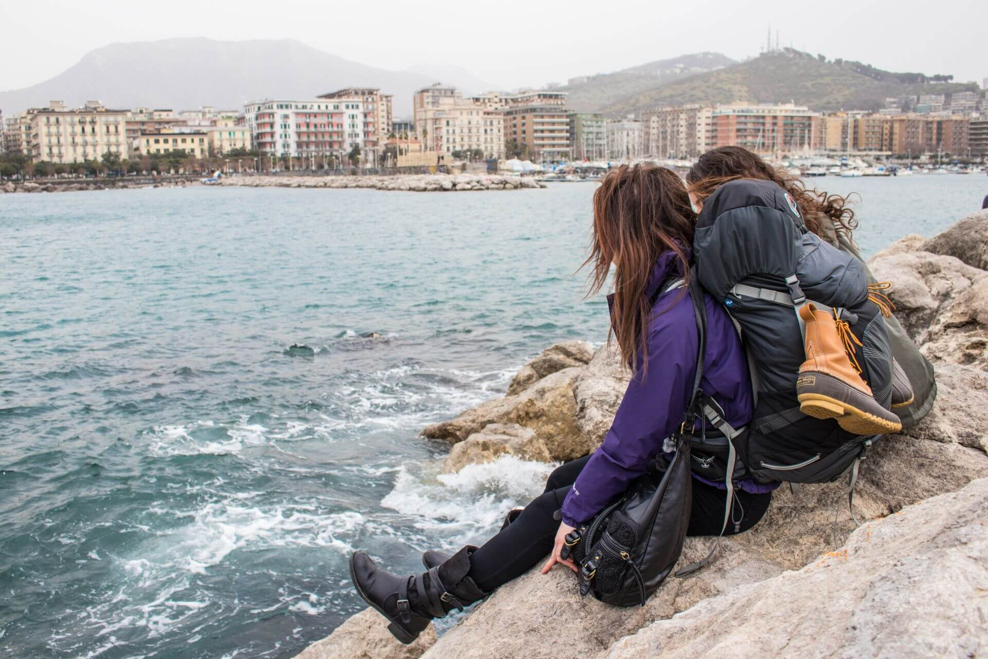Women with backpacks look out over the sea.